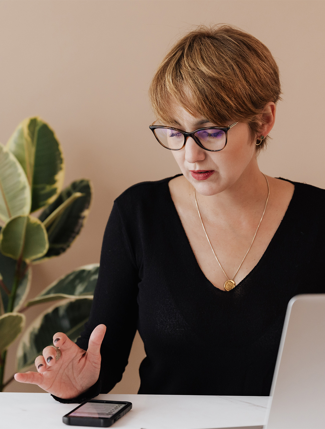 serious-woman-using-mobile-phone-while-working-in-office-4467748 copy